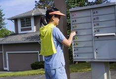 Dojrzała kobieta sprawdza jej poczta przed jej domem zdjęcie royalty free
