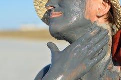 Dojrzała kobieta stosuje kopalnego błoto na twarzy i ręce Fotografia Stock