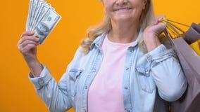 Dojrzała kobieta trzyma dolarowych rachunki z torbami na zakupy, zakup zapłata, kredyt zbiory