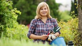 dojrzała kobieta trzyma ogrodniczych narzędzia w ogródzie zdjęcie wideo