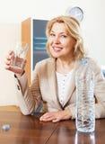 Dojrzała kobieta trzyma szkło wypełniający z wodą Zdjęcia Royalty Free