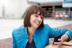 Dojrzała kobieta uśmiechnięta i patrzeje telefon komórkowego Zdjęcie Royalty Free
