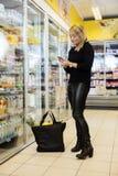 Dojrzała kobieta Używa telefon komórkowego W sklepie spożywczym zdjęcie stock