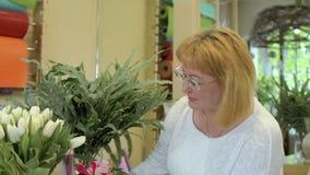 Dojrzała kobieta w kwiatu sklepie zbiory wideo