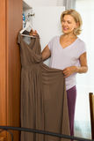 Dojrzała kobieta wybiera suknię w domu Zdjęcia Royalty Free