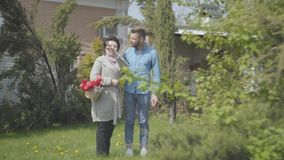 Dojrzała kobieta z koszem z tulipanami opowiada z jej wnukiem na podwórko w rękach Dorosły wnuk i zdjęcie wideo
