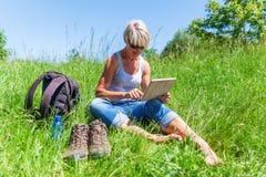 Dojrzała kobieta z stołowym komputerem osobistym przy wycieczkuje odpoczynkiem Obrazy Royalty Free