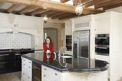 Dojrzała kobiety pozycja W Nowy luksus Dostosowywającej kuchni Zdjęcia Royalty Free