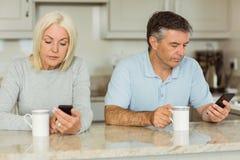 Dojrzała para ma kawowego i używa telefony Zdjęcia Royalty Free