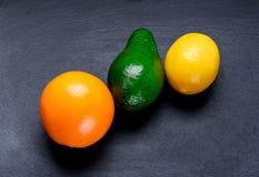 Dojrzała pomarańcze, cytryna i avacado na łupkowej desce, Zdjęcia Royalty Free