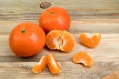 Dojrzała pomarańczowa świeża mandarynka, czysta mandarynka, mandarynka plasterki na drewnianym tle, zdjęcie royalty free