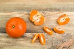 Dojrzała pomarańczowa świeża mandarynka, czysta mandarynka, mandarynka plasterki na drewnianym tle, Odgórny widok fotografia stock