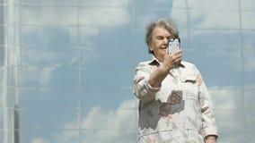Dojrzała stara kobieta bierze fotografie używać mądrze telefon zbiory