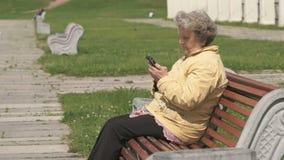 Dojrzała stara kobieta opowiada na telefonie komórkowym outdoors zbiory wideo