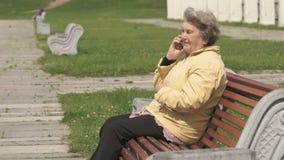 Dojrzała stara kobieta opowiada na telefonie komórkowym outdoors zbiory