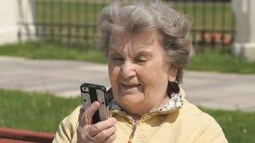 Dojrzała stara kobieta opowiada na telefonie komórkowym outdoors zdjęcie wideo