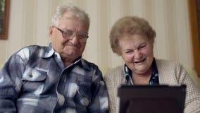 Dojrzała starsza para cieszy się nowożytną technologię używać pastylka komputer osobistego Starsi ludzi komunikuje z internetem w zbiory