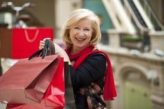 Dojrzała szczęśliwa kobieta z torba na zakupy Fotografia Royalty Free