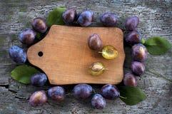 Dojrzałe śliwki wokoło drewnianej deski Obraz Royalty Free