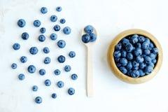 Dojrzałe świeże czarne jagody w drewnianym pucharze na bielu stole Zdjęcia Stock