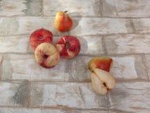 Dojrzałe brzoskwinie, bonkrety, jabłka kłamają na drewnianym stole zdjęcia royalty free