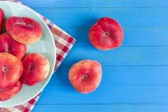 Dojrzałe brzoskwinie na nieociosanym błękitnym drewnianym stole Odgórny widok zdjęcie stock