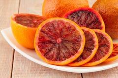 Dojrzałe czerwone krwionośne pomarańcze i plasterki w talerzu Fotografia Stock