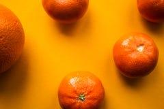 Dojrzałe mandarynki i pomarańcze na pomarańczowym bacground Zdjęcia Royalty Free