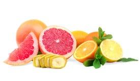 Dojrzałe pomarańcze, świezi grapefruits, soczysta cytryna i plasterki banan z zielonymi cytrusów liśćmi na białym tle, Fotografia Royalty Free