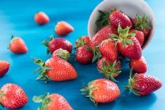 Dojrzałe truskawki w łozinowym koszu na drewnianym stole na błękitnym tle zdjęcia stock
