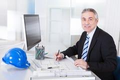 Dojrzałego architekta męski działanie przy biurkiem Zdjęcia Stock