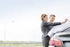 Dojrzałego biznesu koledzy analizuje mapę na zewnątrz samochodu przeciw niebu fotografia stock