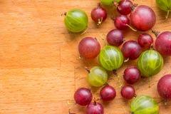 Dojrzały agrest kłama na drewnianej powierzchni Świeży dojrzały czerwieni i zieleni agrest dieta, wegetarianizm, weganinu jedzeni Obrazy Royalty Free