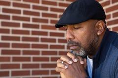 Dojrzały amerykanina afrykańskiego pochodzenia mężczyzna modlenie zdjęcia stock