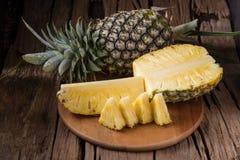Dojrzały ananas i ananasów plasterki na drewnianym tła tropi obraz stock