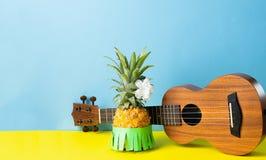 Dojrzały ananas w zielonej hawajczyk spódnicie Małej gitary błękitny żółty tło Pojęcie Hawajski lata przyjęcia karnawał obrazy stock
