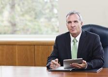 Dojrzały biznesmen używa pastylka komputer zdjęcie royalty free