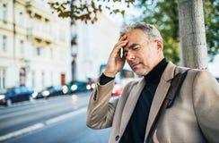 Dojrzały biznesmen w bólowej pozycji na ulicie w mieście, mienia czoło zdjęcia royalty free