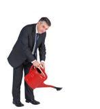 Dojrzały biznesmena podlewanie z czerwienią może Fotografia Stock