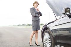 Dojrzały bizneswoman patrzeje awaria samochód na drodze zdjęcia royalty free