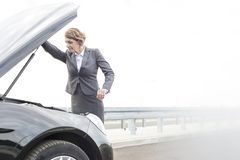 Dojrzały bizneswoman patrzeje awaria samochodowego silnika na drodze przeciw niebu zdjęcia stock