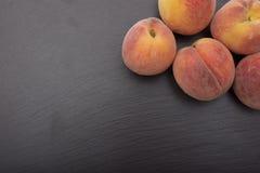 Dojrzały brzoskwinia jonu czerni tło łupek lub kamień Obraz Royalty Free