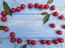 Dojrzały czereśniowy jagodowy organicznie na błękitnym drewnianym tle, sezonowy wzór zdjęcia royalty free