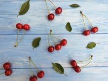 Dojrzały czereśniowy jagodowy organicznie słodki zdrowy smakowity na błękitnym drewnianym tle, sezonowy wzór zdjęcie stock