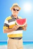 Dojrzały dżentelmen trzyma plasterek arbuz na plaży Zdjęcie Stock