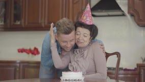 Dojrzały damy obsiadanie przy stołem z urodzinową nakrętką na jej głowie Dorosły wnuk przynosi małego tort i stawia dalej zbiory