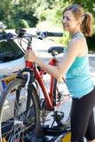 Dojrzały Żeński cyklista Bierze rower górskiego Od stojaka Na samochodzie obraz stock