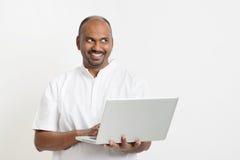 Dojrzały Indiański mężczyzna używa laptop patrzeje stronę Zdjęcia Royalty Free