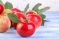 dojrzały jabłko z zielenią opuszcza zakończenie i udziały jabłka w tle na błękitnym drewnianym tle obrazy royalty free