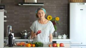 Dojrzały kobieta taniec z czerwoną szpachelką dla naczyń w jej kuchni Nowożytny kuchenny wnętrze, jaskrawi warzywa na zdjęcie wideo